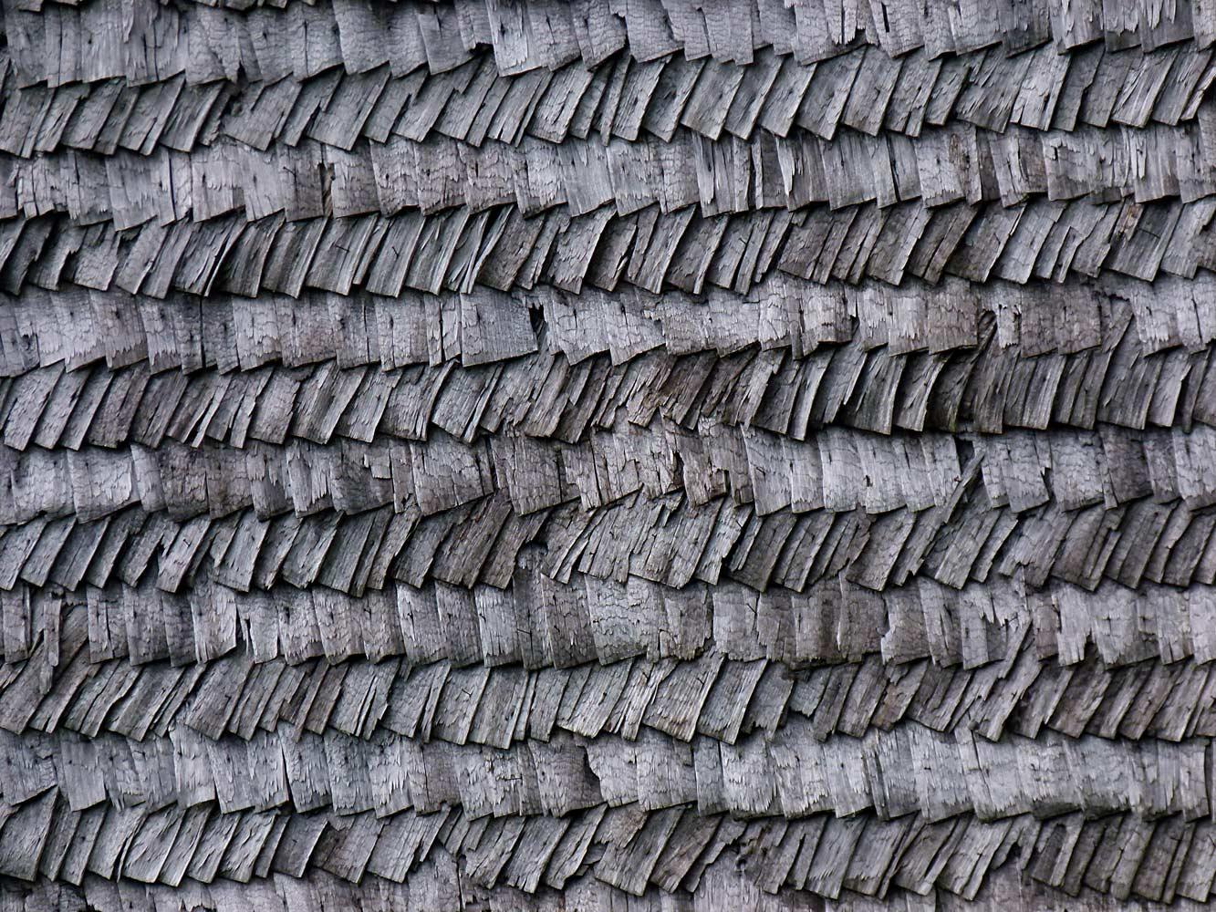 Gros plan sur les tuiles en bois habillant un vieux chalet savoyard.